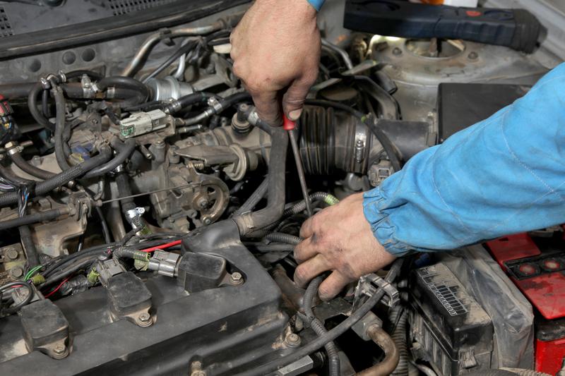 man servicing car engine