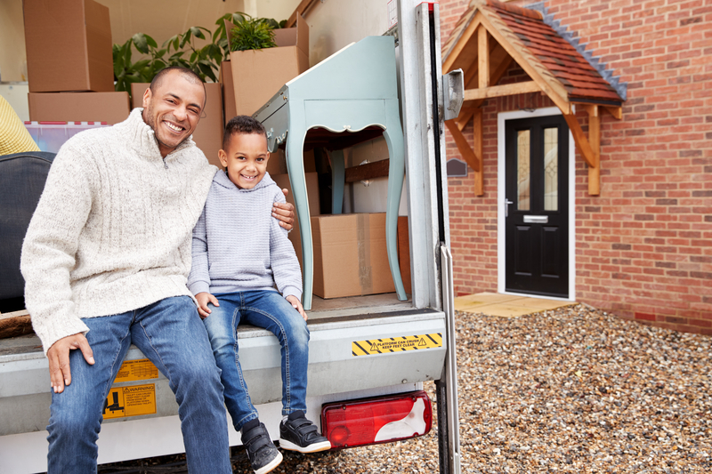 father and son sitting on the edge of the moving van looking very happy